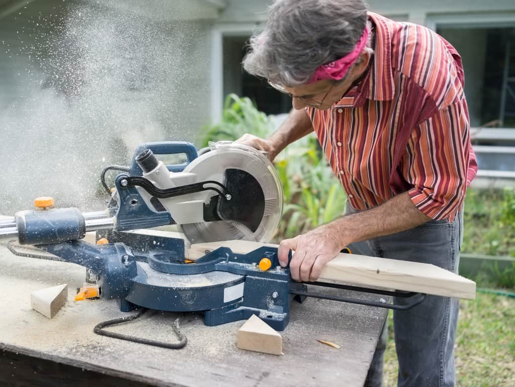 Closeup of mature man sawing lumber with sliding compound miter saw outdoors, sawdust flying around