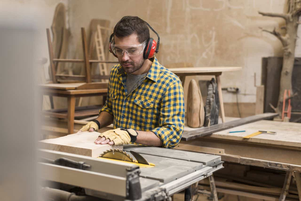 A carpenter is using a table saw