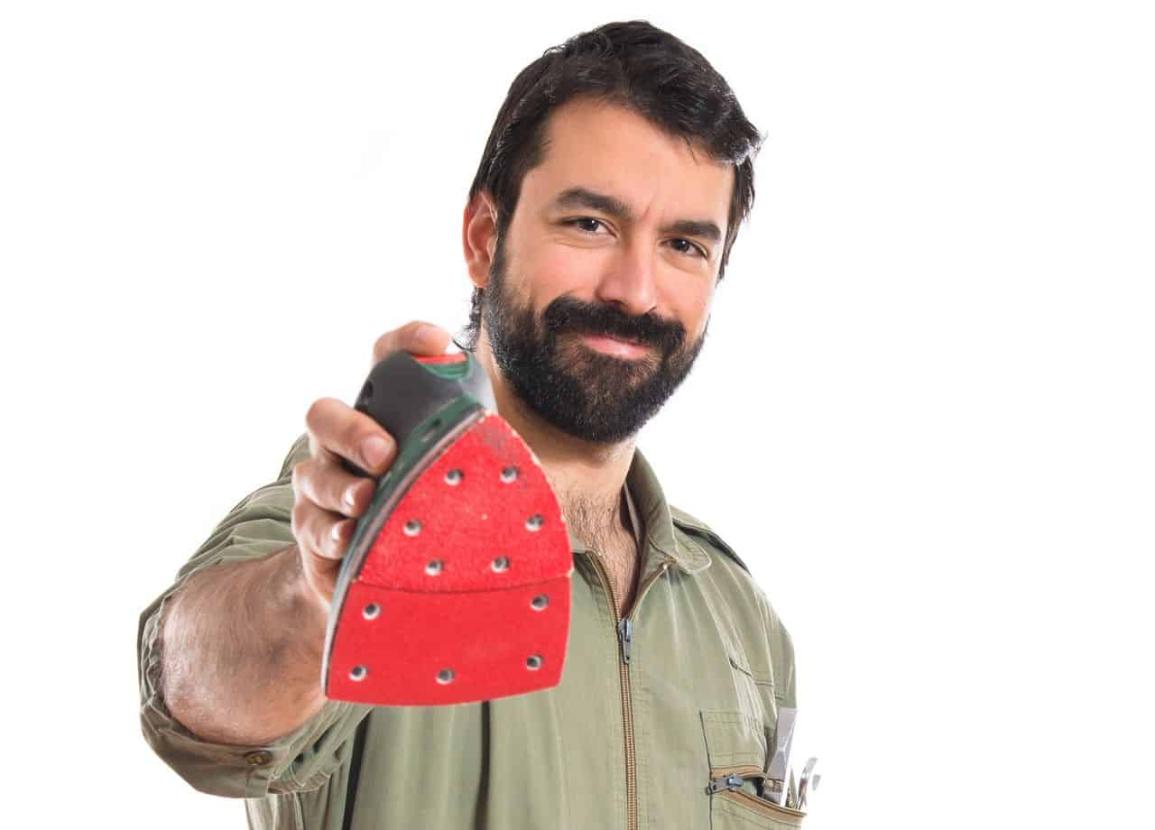 A handyman holding a detail or mouse sander