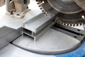 The blade of a miter saw touches an aluminum work piece to cut it