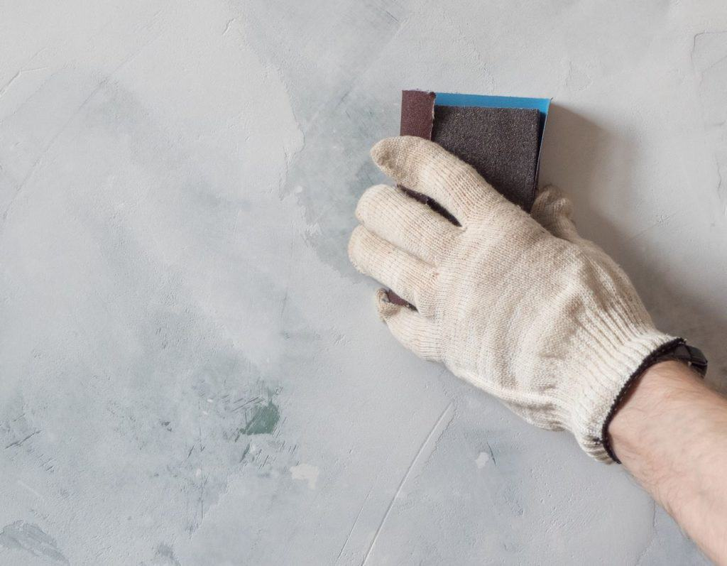 Sanding plaster wall with sandpaper